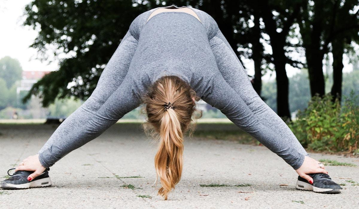 Lenige en sportieve vrouw, onherkenbaar doordat ze voorovergebogen staat