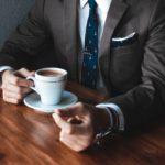 doelgroep website bepalen: Gesticulerende handen van man in zakelijke pak met een kopje koffie